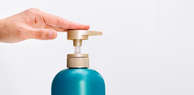 Fundo branco com uma mão pressionando a tampa de um frasco azul   - Qualicorp