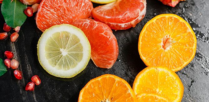 Fundo preto com três gomos de tangerina, uma rodela de limão siciliano, 4 rodelas de laranja e sementes de romã espalhados em cima - Qualicorp