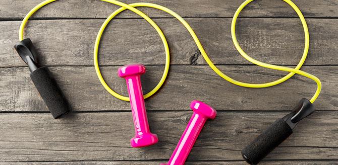 Fundo de madeira marrom escura, sobre ele uma corda de treino amarela com pegadores pretos e ao centro duas barras de peso cor rosa pink - Qualicorp