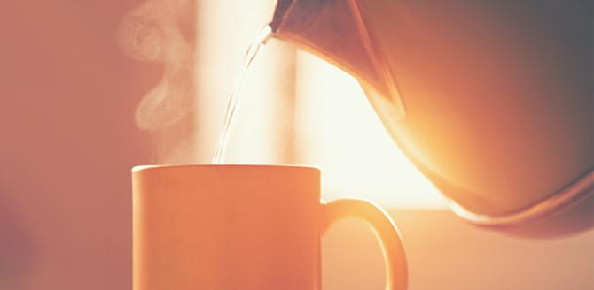Bule despejando água quente em uma xícara de chá, ao fundo uma janela aberta com entrada da luz do sol  - Qualicorp