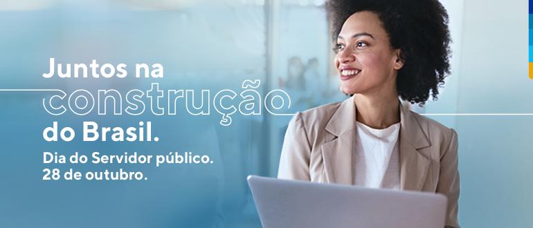Fundo azul, com a foto de uma mulher negra com camiseta branca e terno bege, de pé, segurando notebook branco. E escrito no banner: Juntos na construção do Brasil. Dia do servidor público. 28 de Outubro.
