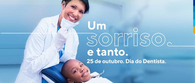Fundo azul, com jovem dentista em pé puxando a máscara para baixo, exibindo sorriso, e jovem paciente sentado na cadeira de dentista sorrindo.