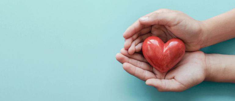 Fundo azul, à direita, duas mãos segurando um coração vermelho.