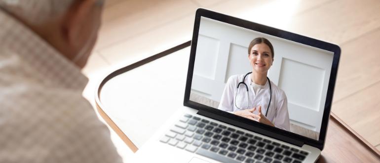 Paciente idoso em frente ao notebook, realizando consulta por telemedicina