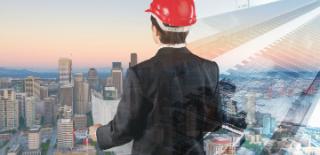 engenheiro olhando para cidade do alto com paletó preto e capacete vermelho