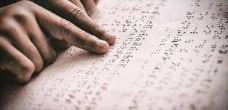 Dois dedos indicadores fazendo leitura de texto em braille