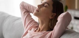 Mulher sentada no sofá com olhos fechados relaxando