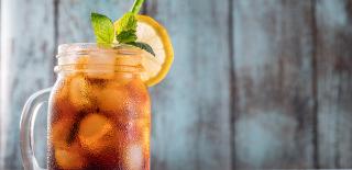 Copo à esquerda da imagem com chá refrescante para o verão, com cubos de gelo decorado com hortelã e rodela de limão