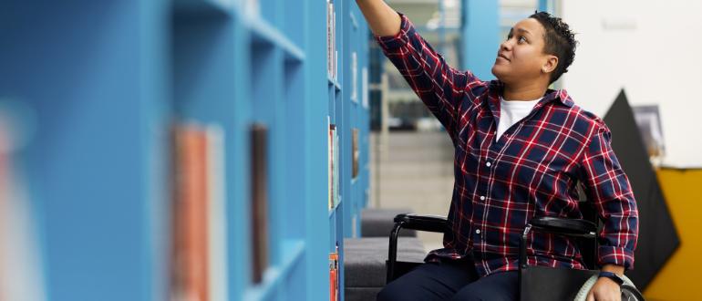 Pessoa, em cadeira de rodas, pegando livro na biblioteca, sorrindo