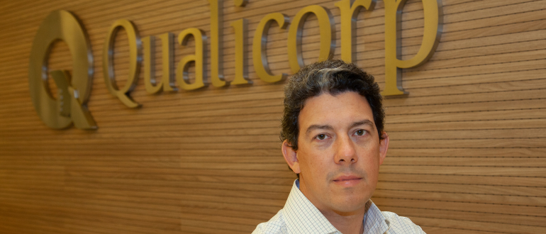 Bruno Blatt em frente ao painel da Qualicorp no prédio da empresa