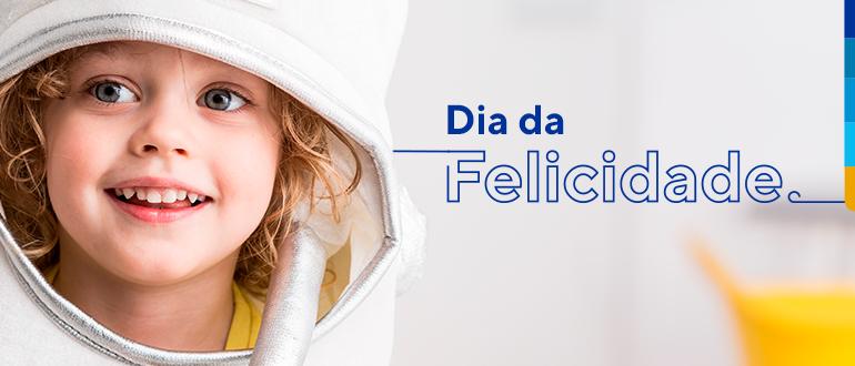 Criança sorrindo dentro de fantasia branca, ao lado texto: Dia da Felicidade