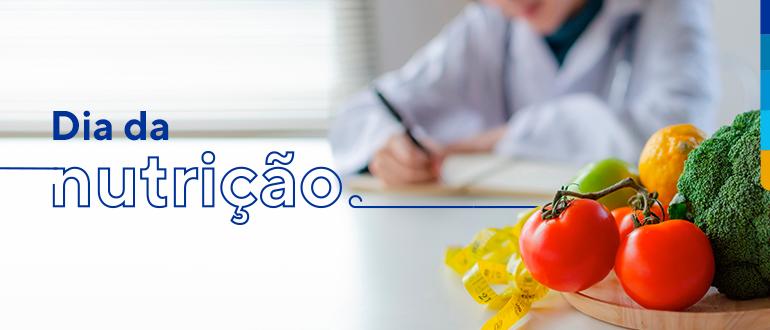 Texto:  Dia da nutrição,. Ao lado, prato com tomates, brócolis, limão siciliano e maçã verde