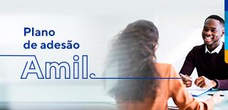 Texto: Plano de adesão Amil. Ao lado, homem sorrindo, sentando com as mãos segurando uma caneta, em frente a uma mulher de cabelos cacheados com blusa laranja.