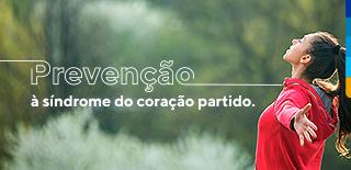 Texto: Prevenção à síndrome do coração partido. Ao lado, mulher de braços abertos e olhos fechados com blusa vermelha.