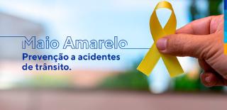 Maio Amarelo. Prevenção a acidentes de trânsito. Ao lado, m]ao masculina segurando laço amarelo