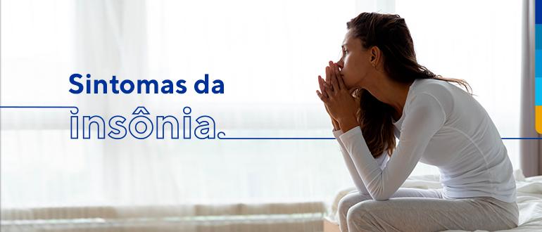 Texto: Sintomas da insônia. Ao lado mulher sentada na cama com roupas brancas olhando na direção da janela.